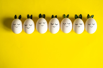 Happy Easter card. Cute Easter eggs with a painted face in a spring leaves on yellow background. Happy Easter