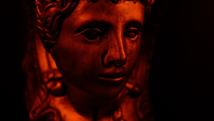 Antique face in red light