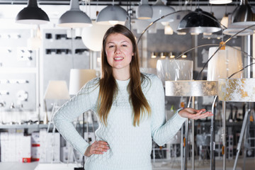 Young female  standing near modern lamp  in the  store