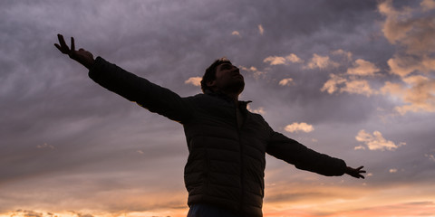 Low angle view of young man standing under glowing evening sky