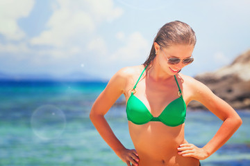 Summer vacation holiday paradise beach picture - Happy smiling Beautiful wet young girl portrait in sunglasses and bikini walking on the coast sand with sea on background paradise
