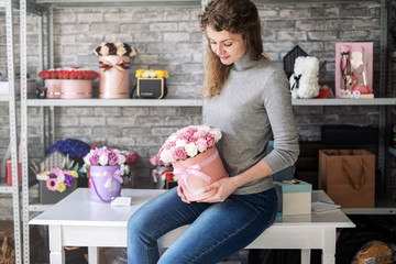 The florist girl is sitting on the table in the workshop and holding a round pink box with a bouquet of roses.
