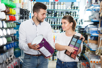 Couple choosing paint in household store