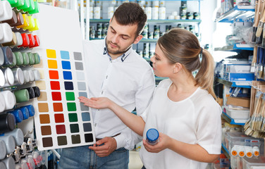 man and woman select colors of paint