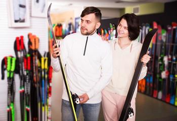 Couple choosing skis in shop