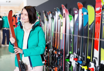 Young happy woman shopper choosing new skis in sports shop