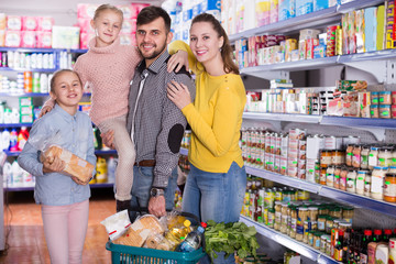 family  holding full basket after shopping