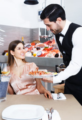 Waiter bringing seafood to guests