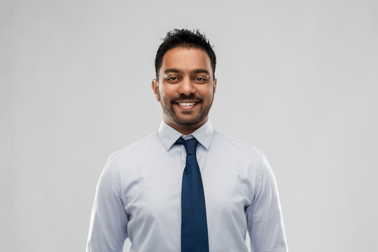 business, office worker and people concept - smiling indian businessman in shirt with tie over grey background