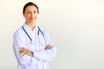 Femal doctor in white gown with stethoscope looking at camera in self-confidence manner