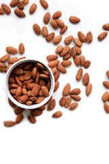 Natural background made in nuts. White background with bowl of almonds.