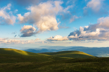 wonderful evening landscape. beautiful view from the grassy hill in to the distant valley and mountain ridge. fluffy clouds on the sky. peaceful idyllic scenery