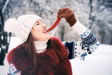 The girl holds in her hand a sharp red chili pepper. Young beautiful woman in a winter park.