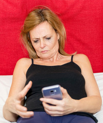 Moment of despair of a woman who is looking at the display of her smartphone