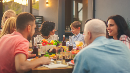 Big Family Garden Party Celebration, Gathered Together at the Table Relatives and Friends, Young and Elderly are Eating, Drinking, Passing Dishes, Joking and Having Fun. Mother Asks Her Son.