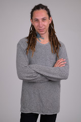 Portrait of happy young man with dreadlocks smiling while crossing arms