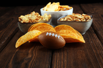 Chips, salty snacks, football on a table. Great for Bowl Game