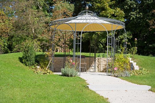 Vintage Gartengestaltung: Kiesweg zum Pavillon und zur Terrasse mit einer Mauer aus Natursteinen