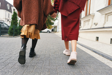 Two girls walking on city street in a stylish outfit