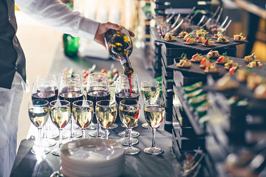 The waiter pours wine into glasses. Event catering concept.