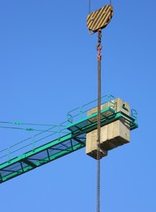Low angle view of a hook block hovering at altitude, with a green construction crane and counterweights in the background, Tirana, Albania
