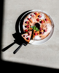 Cake with Raspberry on gray background .Cake with  fresh berries. Homemade Sweet Dessert.Top View. selective focus.Bright Hard Sunlight Deep Shadow.