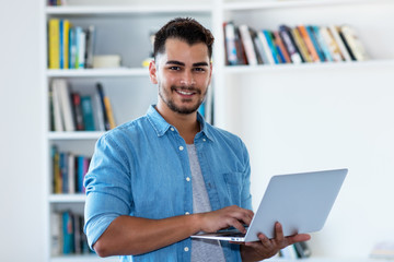 Mexican hipster man with beard and computer