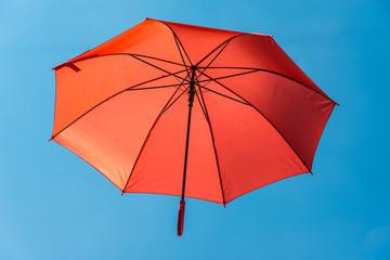 Roter Regenschirm im blauen Himmel