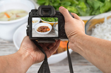 Food phototography concept. Man's hands holding a DSLR camera taking picture of an Asian meal set