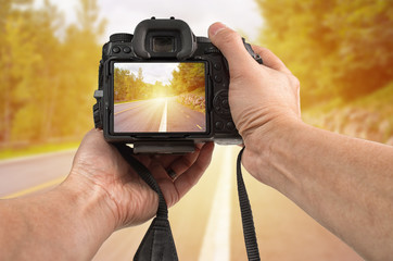 Travel phototography concept. Man's hands holding a DSLR camera taking picture of a street