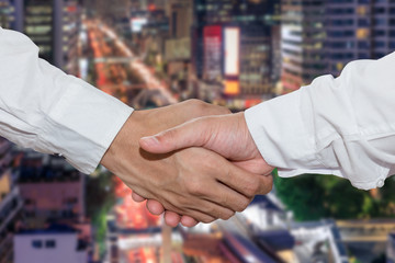 Business people shake hand in front of financial district at night
