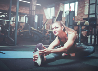 Training and sport concept, woman stretching leg at gym