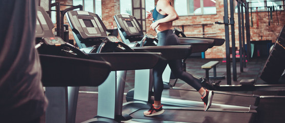 Healthy woman running on a treadmill in a gym. Sport and health concept.