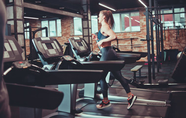 Young sports woman doing cardio training on treadmill. Running on treadmill at gym.