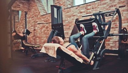 Sportswoman flexing muscles on leg press machine in gym. The training process, legs workout, fitness. back view...
