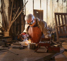 A senior white-haired man in his DIY shop soldering metal parts