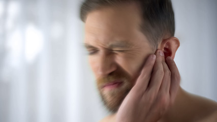 Man feels pain in middle ear, meningitis and hearing loss, inflammation, closeup