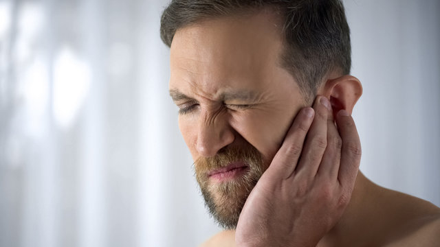 Man holding his aching ear, suffering from otitis, sudden hearing loss, close up