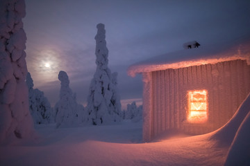 Illuminated snow covered log cabin in the forest at night during winter
