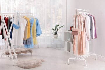 Racks with stylish clothes in light room