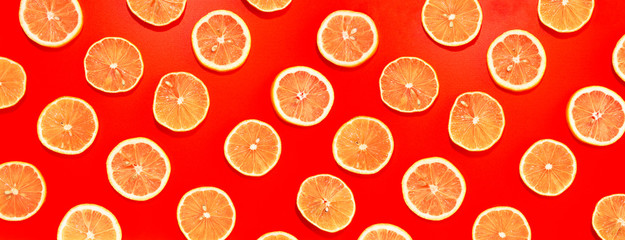 Wall Mural - Lemon slices in lines with hard shadows on red background, flat lay image.