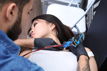 Professional artist making tattoo with machine in salon