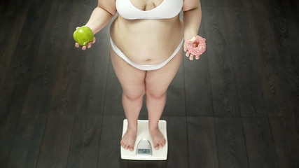Chubby woman standing on scales with apple and bitten donut, choosing sweets