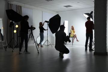 Blurred photo studio with professional equipment and team of workers
