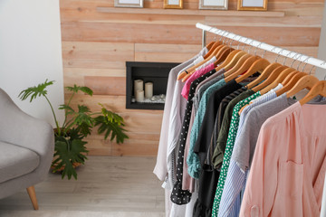 Wardrobe rack with stylish clothes in dressing room