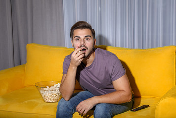 Emotional man watching with popcorn TV on couch in living room