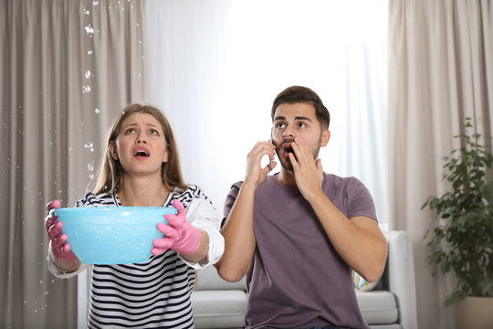 Emotional young woman collecting water leaking from ceiling while her husband calling plumber in living room