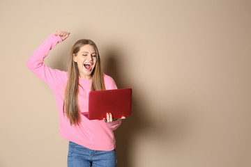 Emotional young woman with laptop celebrating victory on color background. Space for text