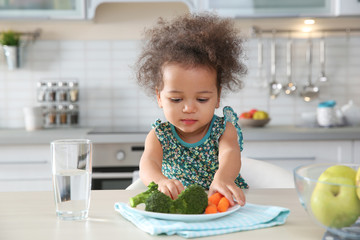 Cute African-American girl eating vegetables at table in kitchen