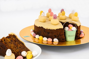 Easter Simnel Cake. Easter Simnel Cake with marzipan icing and eleven balls of marzipan representing the twelve Apostles minus Judas. with buckets of chocolate mini eggs and Easter chicks .